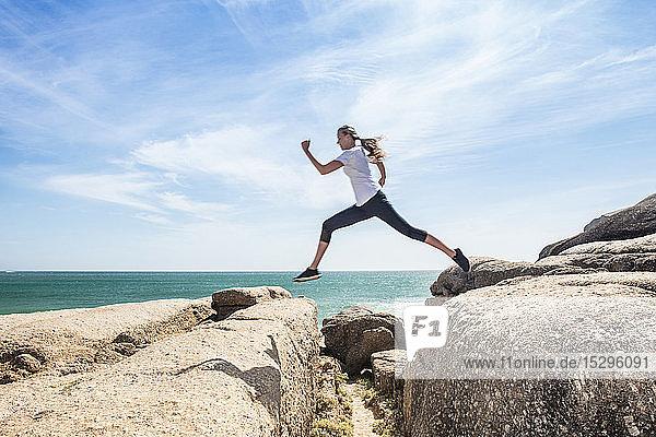 Junge Läuferin springt über Strandfelsen,  in voller Länge,  Kapstadt,  Westkap,  Südafrika