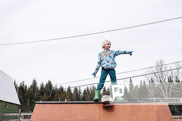Junge steht oben auf der Skateboard-Rampe und zeigt