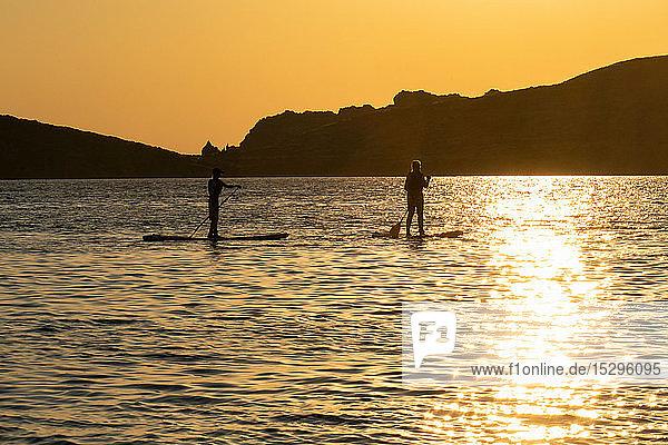 Mutter und Sohn paddeln im Meer bei Sonnenuntergang  Limnos  Khios  Griechenland Mutter und Sohn paddeln im Meer bei Sonnenuntergang, Limnos, Khios, Griechenland