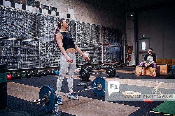 Junger Mann beobachtet Frau  die sich im Fitnessstudio darauf vorbereitet  Langhantel zu heben