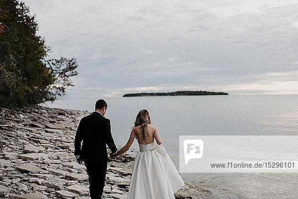 Romantische junge Braut und Bräutigam schlendern am Hochzeitstag am Seeufer entlang