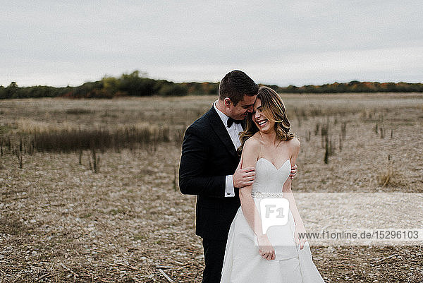 Romantisches junges Paar auf dem Feld am Hochzeitstag