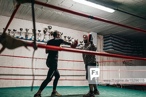 Boxer sparring with trainer in boxing ring