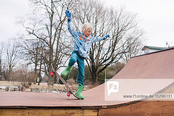 Junge auf ländlicher Skateboard-Rampe beim Üben eines Skateboard-Tricks