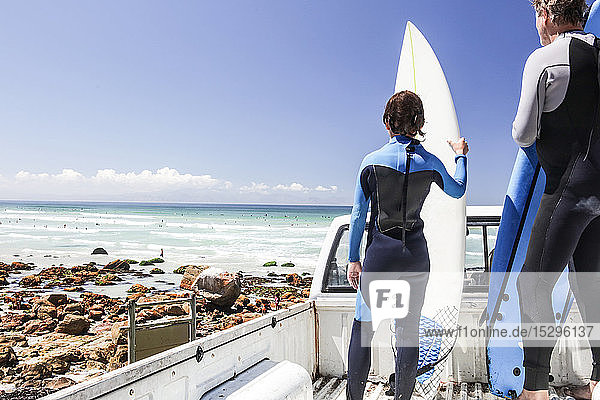 Boy surfer and father standing on back of truck looking out to sea  rear view  Cape Town  Western Cape  South Africa