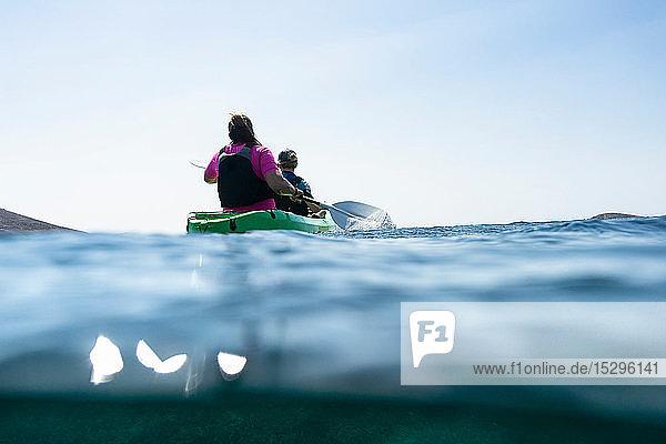 Teenager Junge und Mutter beim Seekajakfahren  Rückansicht auf Bodenhöhe  Limnos  Khios  Griechenland Teenager Junge und Mutter beim Seekajakfahren, Rückansicht auf Bodenhöhe, Limnos, Khios, Griechenland