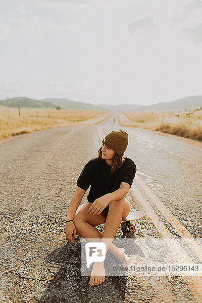 Young female skateboarder sitting on rural road  Exeter  California  USA