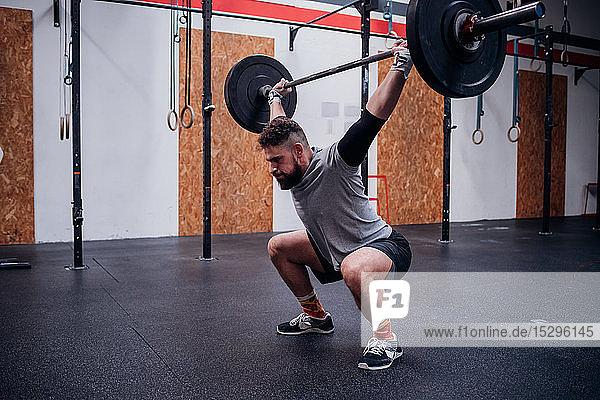 Junger Mann hockt und hebt Langhantel im Fitnessstudio