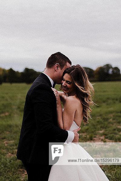 Romantische junge Braut und Bräutigam umarmen sich auf dem Feld