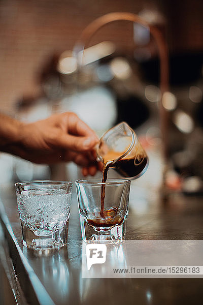 Barista pouring fresh coffee into drinking glass on cafe counter  detail of hand