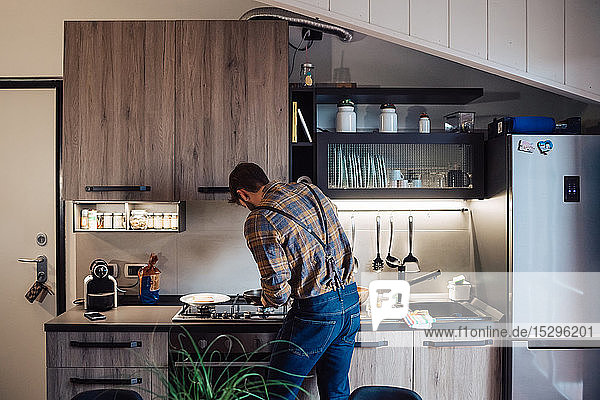 Mid adult man preparing food at kitchen hob  rear view