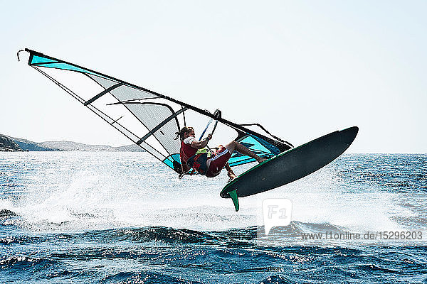 Junger Mann beim Windsurfen über den Wellen des Ozeans  Limnos  Khios  Griechenland Junger Mann beim Windsurfen über den Wellen des Ozeans, Limnos, Khios, Griechenland