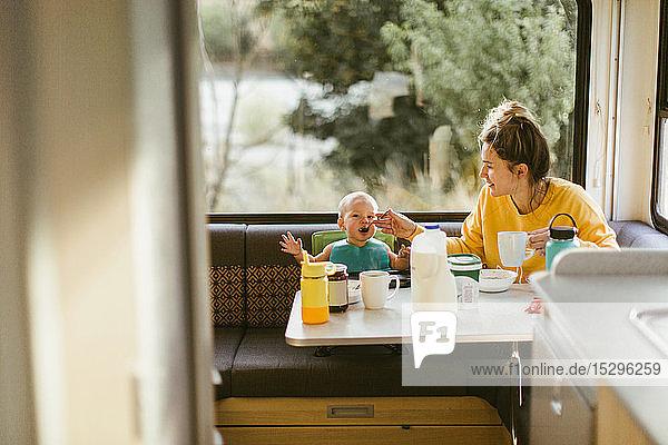 Mother feeding baby breakfast in motorhome