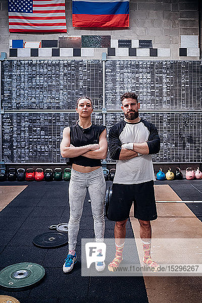 Young couple posing with arms crossed in gym