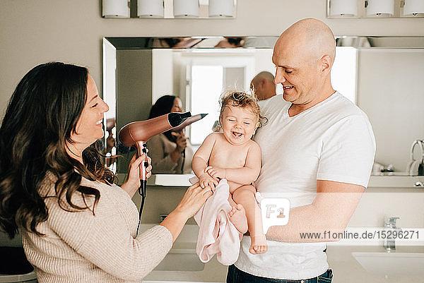 Mutter und Vater trocknen die Haare ihrer Tochter im Badezimmer