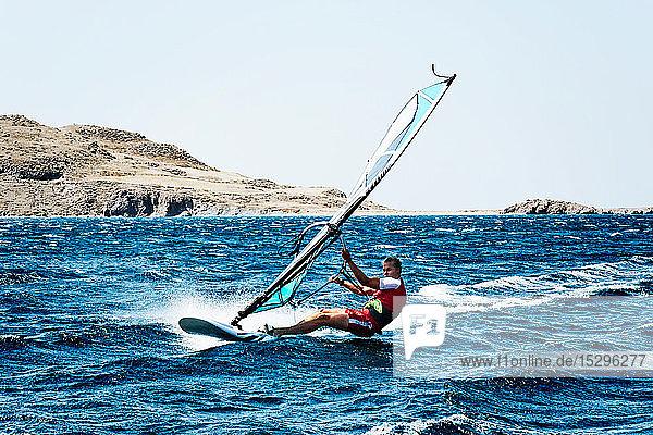 Junger Mann beim Windsurfen auf Meereswellen  Limnos  Khios  Griechenland Junger Mann beim Windsurfen auf Meereswellen, Limnos, Khios, Griechenland