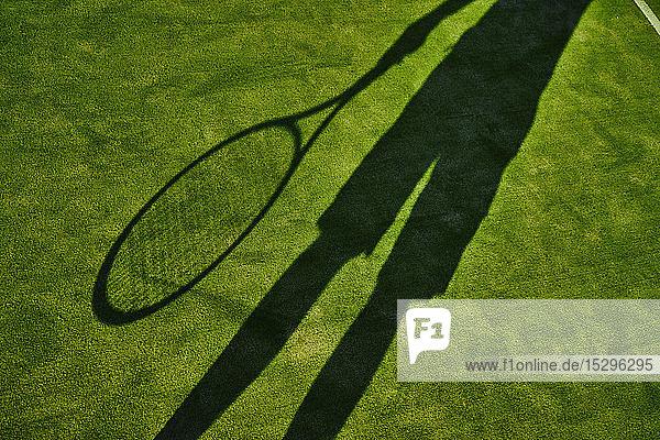 Gestutzter Schatten eines Tennisspielers mit Tennisschläger auf grünem Rasen Gestutzter Schatten eines Tennisspielers mit Tennisschläger auf grünem Rasen