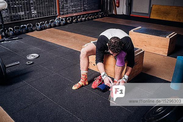 Man tying shoelace in gym