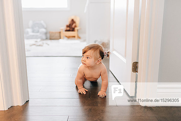 Baby girl crawling through nursery doorway