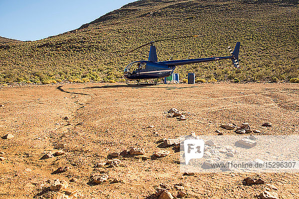 Hubschrauber und Pilot in ländlicher Umgebung  Kapstadt  Westkap  Südafrika