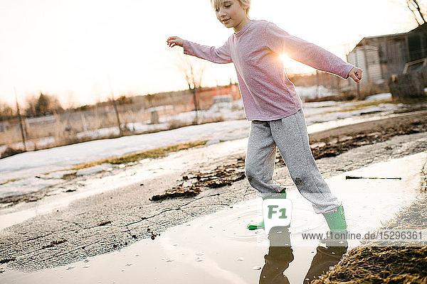 Junge spielt in ländlicher Schmelzwasserpfütze