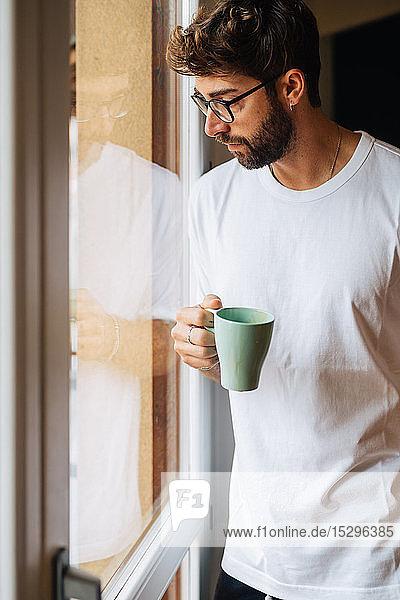 Mittelgroßer erwachsener Mann mit Kaffee  der durch ein Wohnungsfenster hinaussieht