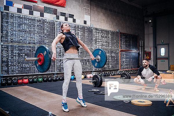 Junger Mann beobachtet Frau beim Hanteln im Fitnessstudio