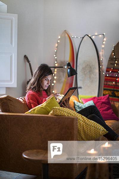 Junge Frau auf Wohnzimmer-Sofa mit digitalem Tablet-Touchscreen