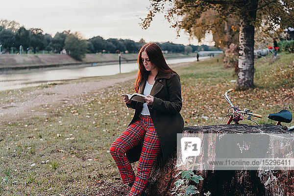 Young woman with long red hair reading book on riverside  Florence  Tuscany  Italy