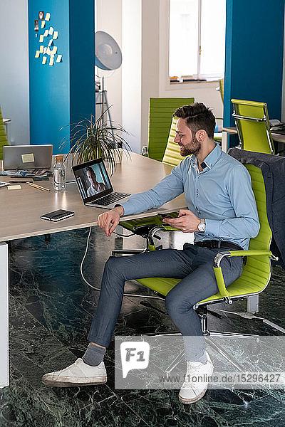 Junger männlicher Geschäftskreativer  der eine Videokonferenz mit einem Kunden auf einem Büro-Laptop führt