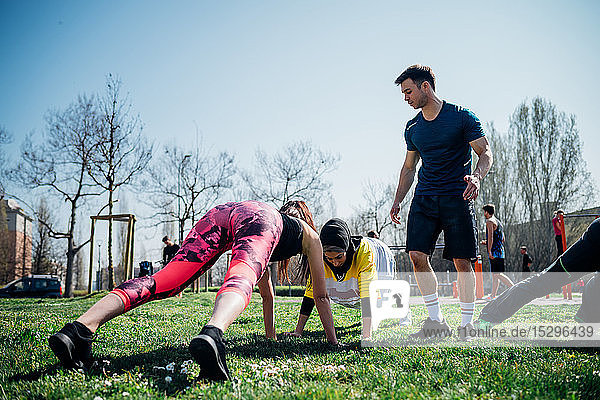 Calisthenics class at outdoor gym  instructor supporting women practicing yoga