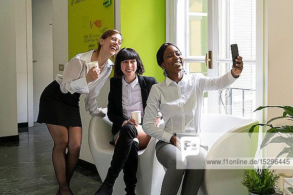 Drei Unternehmerinnen machen eine Pause und machen Smartphone-Selfie im Büro
