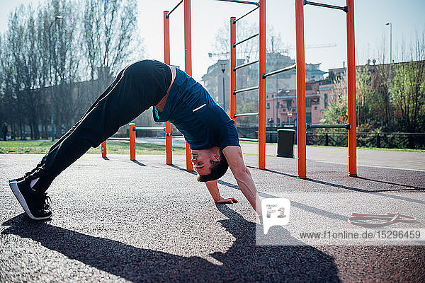 Calisthenics at outdoor gym  young man in downward dog yoga pose