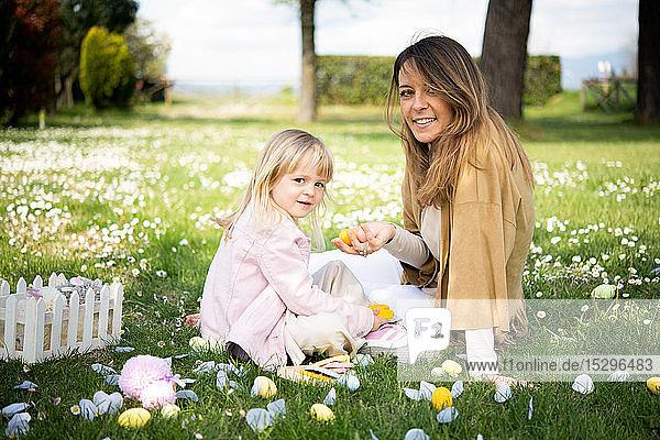 Mutter und Tochter entspannen sich im Wildblumenfeld nach der Ostereiersuche  Porträt  Arezzo  Toskana  Italien