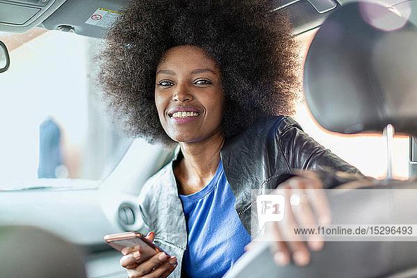 Glückliche junge Frau mit Afro-Haaren auf dem Beifahrersitz eines Autos  die ein Smartphone hält  Porträt