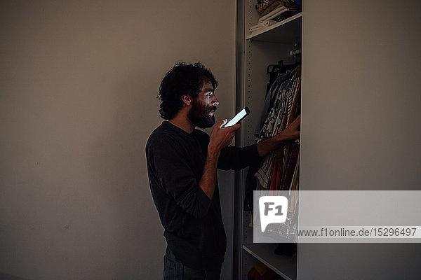 Bearded young man talking on smartphone in front of wardrobe