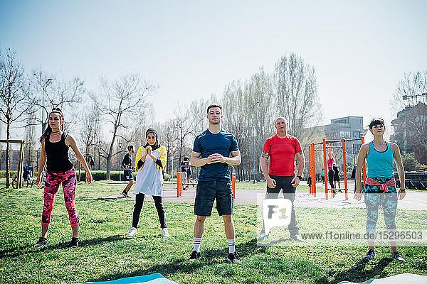 Calisthenics-Unterricht im Fitnessstudio im Freien  Yoga praktizierende Frauen und Männer
