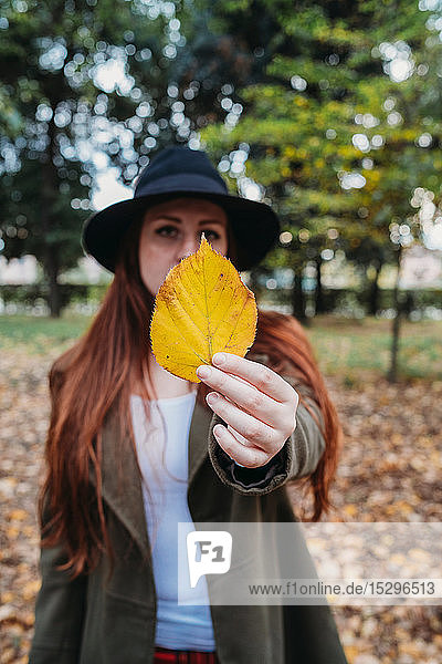 Young woman with long red hair holding up autumn leaf in park  portrait