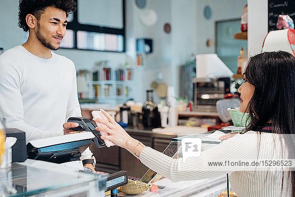 Junge Geschäftsfrau macht Smartphone-Zahlungen am Café-Schalter