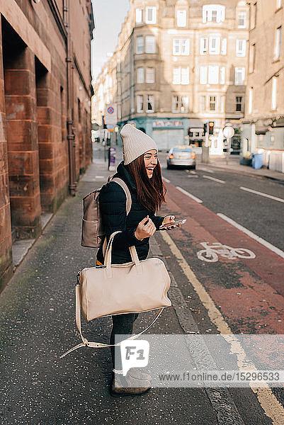 Frau wartet am Bordstein mit Handy und Gepäck  Edinburgh  Schottland