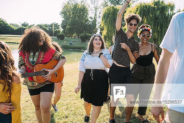 Gruppe von Freunden tanzt  spielt Gitarre im Park