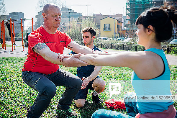 Calisthenics class at outdoor gym  instructor supporting man and woman practicing yoga
