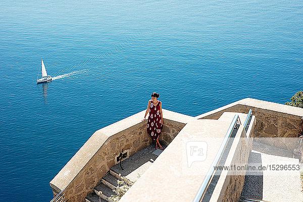Junge Frau genießt den sonnigen Tag auf See  Segelboot im Hintergrund  Alghero  Sardinien  Italien