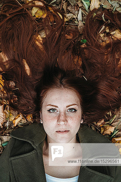 Young woman with long red hair lying amongst autumn leaves  overhead portrait