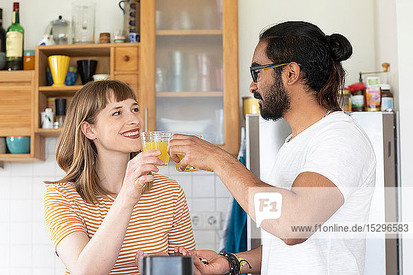 Multi-ethnic couple toasting with juice in kitchen