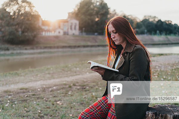 Young woman with long red hair sitting on tree stump reading book on riverside at sunset  Florence  Tuscany  Italy