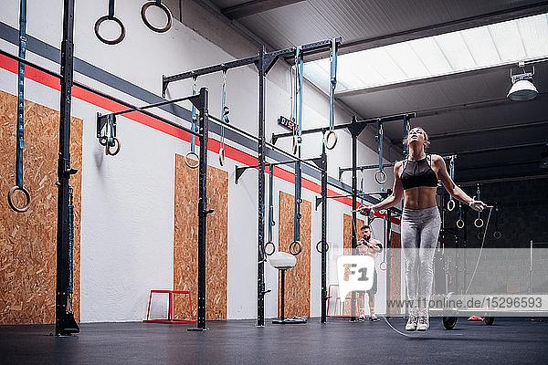 Junge Frau beim Training  Springen im Fitnessstudio  in voller Länge