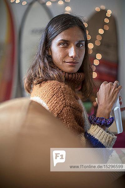 Junge Frau im Strickpulli  die sich auf dem Wohnzimmersofa entspannt und über die Schulter schaut  Porträt