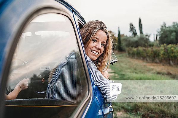 Frau streckt den Kopf aus dem Autofenster