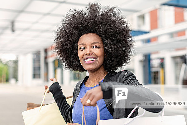 Junge Frau mit Afro-Haaren am Stadtbahnhof  die Einkaufstaschen hochhält  Porträt